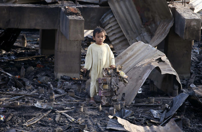 <p>A boy holds a burnt doll house he sifted through the debris following an overnight fire that razed through a coastal village in Bacoor township, Cavite province southwest of Manila, Philippines, April 6, 2017. Fire authorities are still investigating the cause of the fire that damaged more than 600 houses and rendered homeless to more than a thousand families. (Photo: Bullit Marquez/AP) </p>