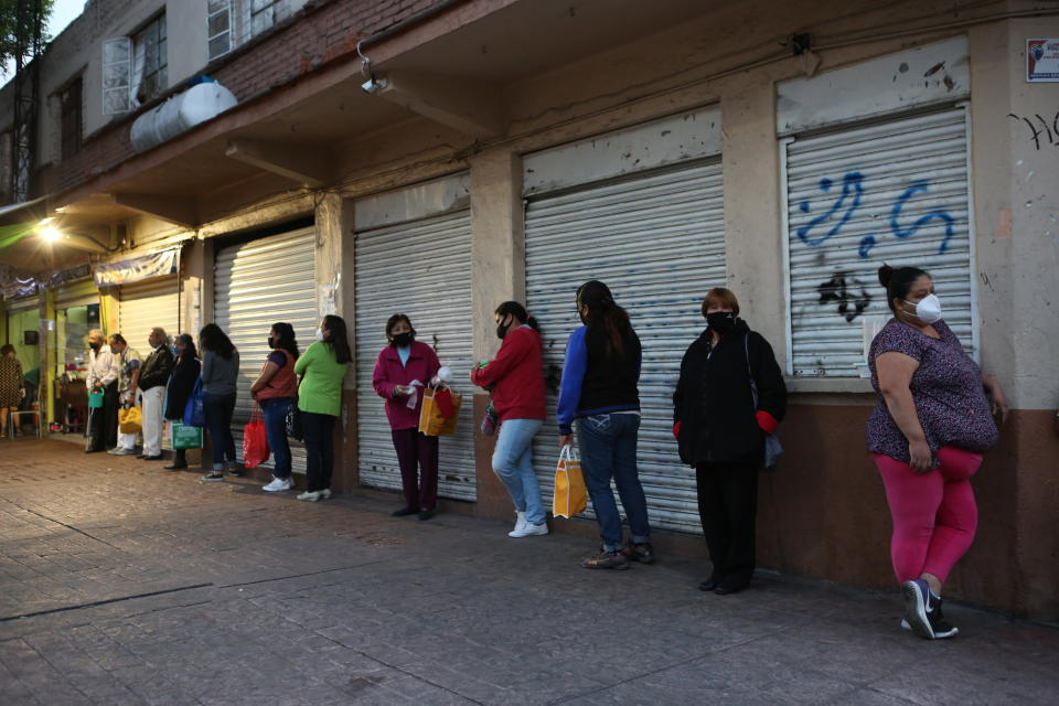 People line up for a free dinner at a soup kitchen in Mexico City, Saturday, Dec. 19, 2020, amid the COVID-19 pandemic. This soup kitchen is operated by neighbors who are in charge of preparing food and serving it to the public for free. The Secretariat of Inclusion and Social Welfare of Mexico City started its soup kitchen program in 2009. (AP Photo/Ginnette Riquelme)