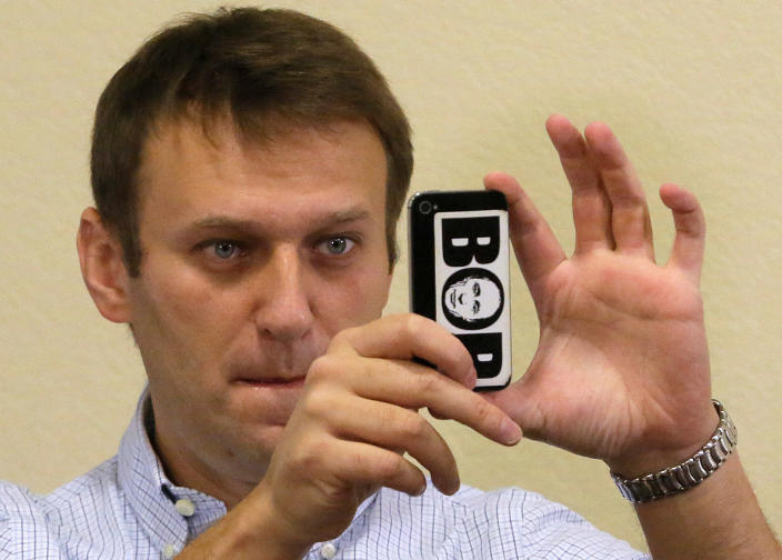 """Russian opposition leader Alexei Navalny takes a photo by his cell phone with a portrait of Russian President Vladimir Putin and words """"Thief"""" in a court room in Kirov, Russia, Wednesday, Oct. 16, 2013. A Russian courthouse in Kirov set Navalny free in July, the day after he was convicted of embezzlement and sentenced to five years in prison. Navalny has appealed both the conviction and the sentence. (AP Photo/Dmitry Lovetsky)"""