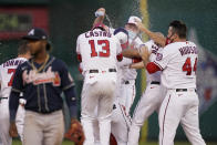 Teammates celebrate with Washington Nationals' Juan Soto in front of Atlanta Braves second baseman Ozzie Albies after Soto hit a game-winning single in the ninth inning of an opening day baseball game at Nationals Park, Tuesday, April 6, 2021, in Washington. Victor Robles scored on the play, and Washington won 6-5. (AP Photo/Alex Brandon)