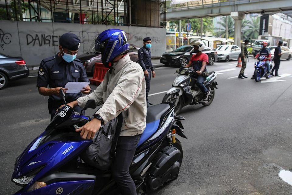 A policeman inspects a motorist's travel documents during a roadblock on Jalan Syed Putra in Kuala Lumpur October 14, 2020. — Picture by Yusof Mat Isa