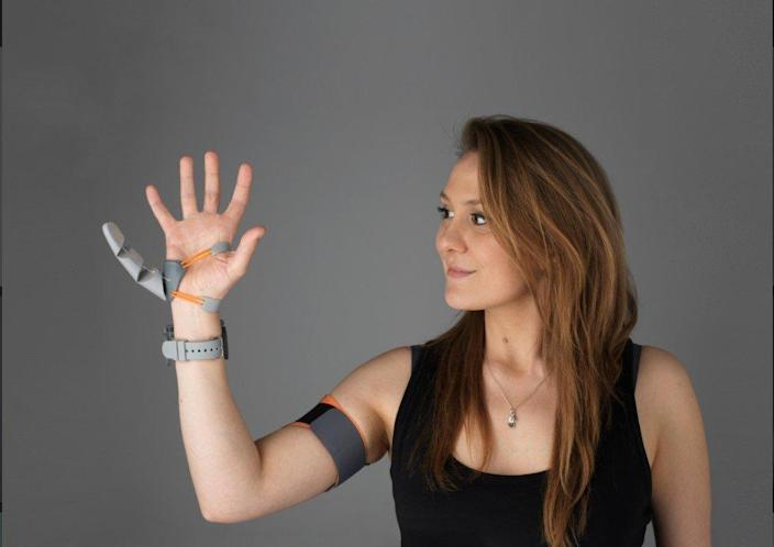 Young woman models th 3d printed, customizable Third Thumb prosthetic.