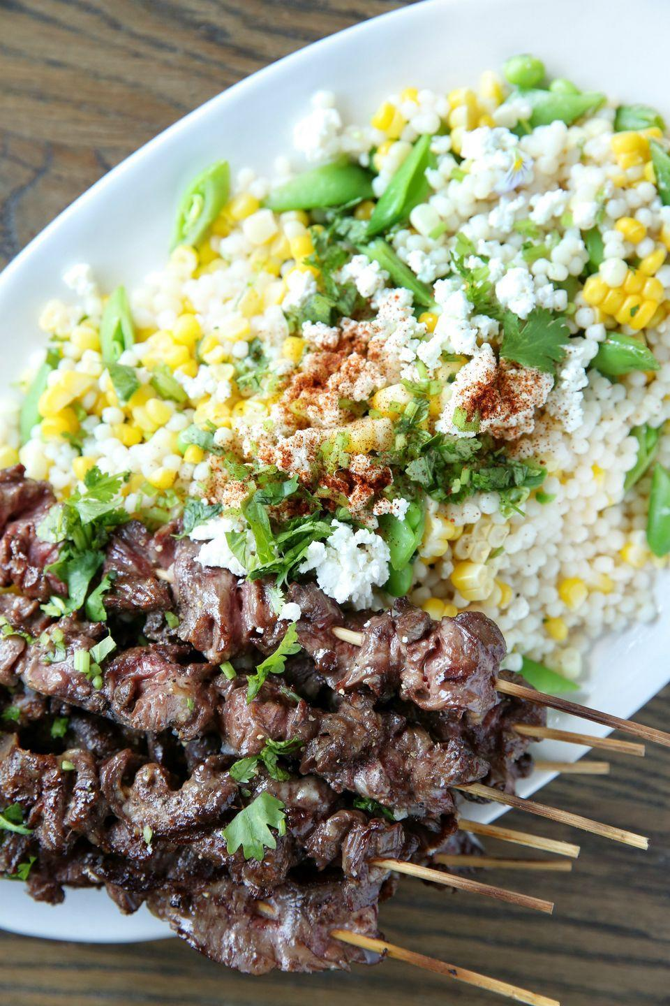 """<p>Step up your summer dinner game with grilled steak kabobs and elote-inspired salad.</p><p>Get the recipe from <a href=""""https://www.delish.com/cooking/recipe-ideas/recipes/a48350/steak-skewers-with-mexican-corn-couscous-salad-recipe/"""" rel=""""nofollow noopener"""" target=""""_blank"""" data-ylk=""""slk:Delish"""" class=""""link rapid-noclick-resp"""">Delish</a>.</p>"""