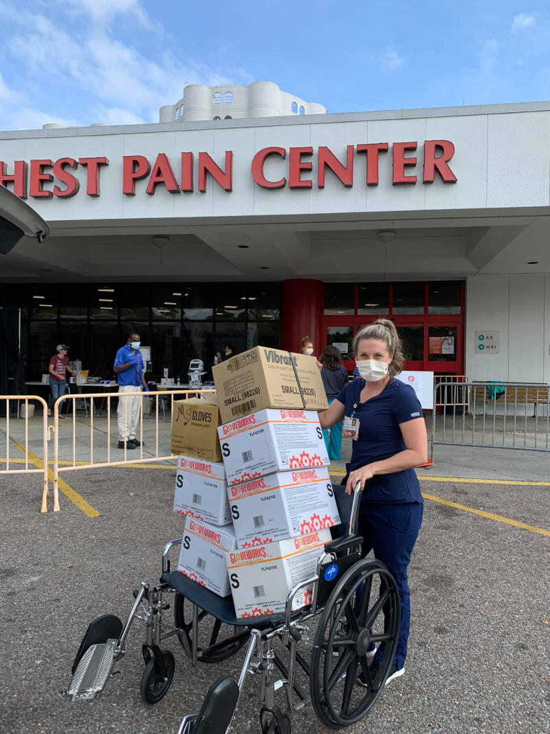 A healthcare worker in Mobile, Alabama, carries boxes of gloves and masks that were donated by local nail salons. (Hien My Pham)