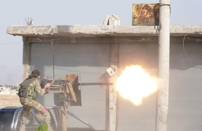 A Turkey-backed Syrian rebel fighter fires a weapon in the town of Tal Abyad, Syria Oct. 13, 2019. (Photo: Khalil Ashawi/Reuters)