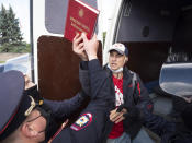 """Police detain a protester holding a """"Red Book of Khabarovsk region"""" during a rally supporting Khabarovsk region's governor Sergei Furgal in St.Petersburg, Russia, Saturday, Aug. 1, 2020. Thousands of demonstrators rallied Saturday in the Russian Far East city of Khabarovsk to protest the arrest of the regional governor, continuing a three-week wave of opposition that has challenged the Kremlin. (AP Photo/Dmitri Lovetsky)"""