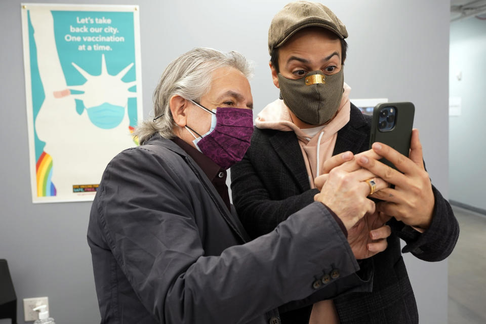 Actor Lin-Manuel Miranda, right, and his father, Luis A. Miranda, Jr., look at a mobile phone before they tour the grand opening of a Broadway COVID-19 vaccination site intended to jump-start the city's entertainment industry, in New York, Monday, April 12, 2021. (AP Photo/Richard Drew, Pool)