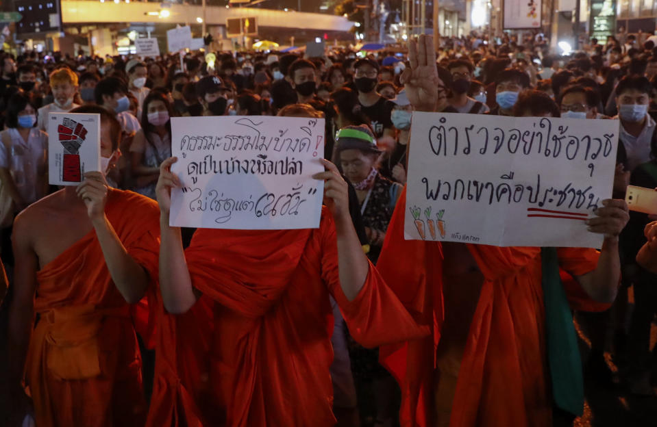 """Buddhist monks supporters of pro-democracy protesters display placards as they march to the German Embassy in central Bangkok, Thailand Monday, Oct. 26, 2020. As lawmakers debated in a special session in Parliament that was called to address political tensions, the students-led rallies were set to continue with a march through centeral Bangkok Monday evening to the German Embassy, apparently to bring attention to the time King Maha Vajiralongkprn spends in Germany. Placards from left read: """"Do you ever watch Dharma program? Or you watch only Nation channel, Police, do not use any weapon, because they are the people."""" (AP Photo/Gemunu Amarasinghe)"""
