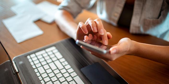 hands holding phone and laptop texting