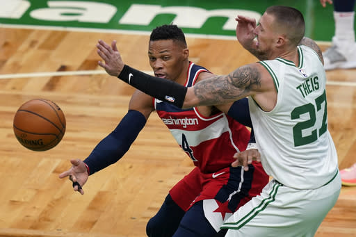 Washington Wizards guard Russell Westbrook (4) passes the ball under pressure from Boston Celtics center Daniel Theis (27) during the first quarter of an NBA basketball game Friday, Jan. 8, 2021, in Boston. (AP Photo/Elise Amendola)