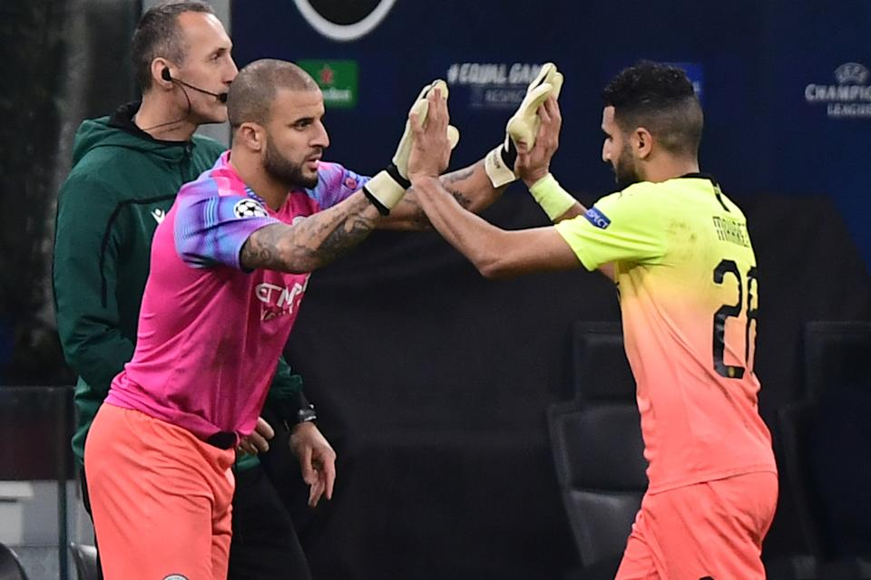 Manchester City's English defender Kyle Walker (L) taps hands with Manchester City's Algerian midfielder Riyad Mahrez as he enters the pitch as a replacing goalkeeper during the UEFA Champions League Group C football match Atalanta Bergamo vs Manchester City on November 6, 2019 at the San Siro stadium in Milan. (Photo by Miguel MEDINA / AFP) (Photo by MIGUEL MEDINA/AFP via Getty Images)
