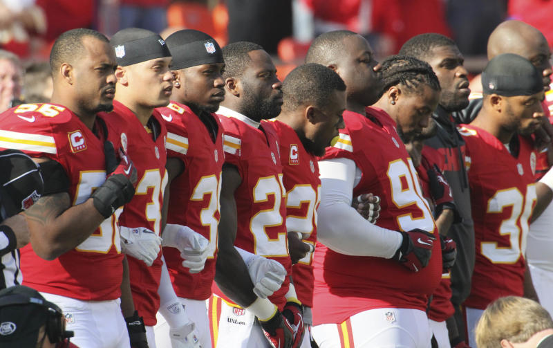 Kansas City Chiefs players stand arm-in-arm during a moment of silence before an NFL football game against the Carolina Panthers at Arrowhead Stadium in Kansas City, Mo., Sunday, Dec. 2, 2012. (AP Photo/Colin E. Braley)