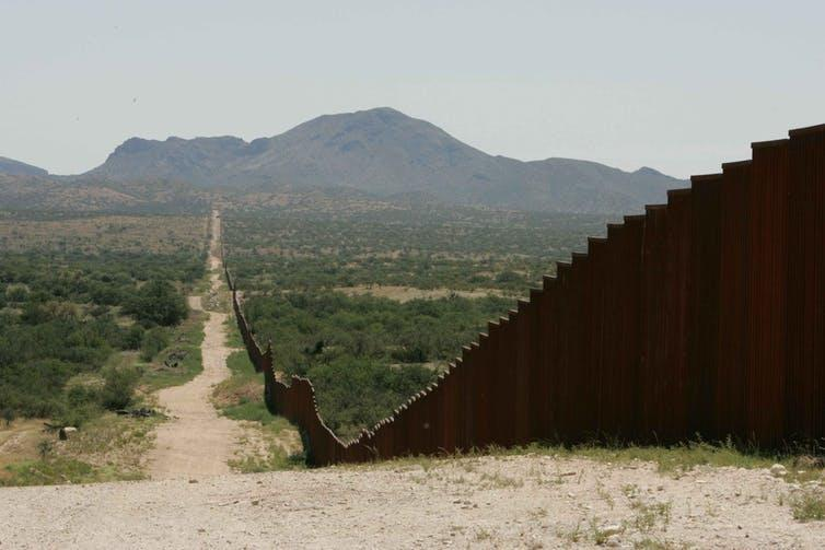 A border wall running along a dirt track in a hot, dry plain.
