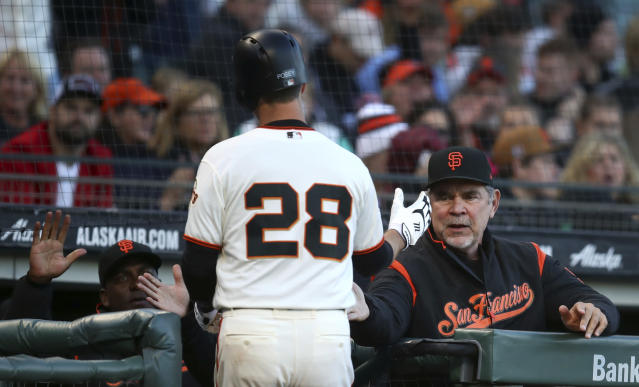 San Francisco Giants' Buster Posey (28) is congratulated by manager Bruce Bochy, right, after scoring against the Miami Marlins in the second inning of a baseball game Monday, June 18, 2018, in San Francisco. (AP Photo/Ben Margot)