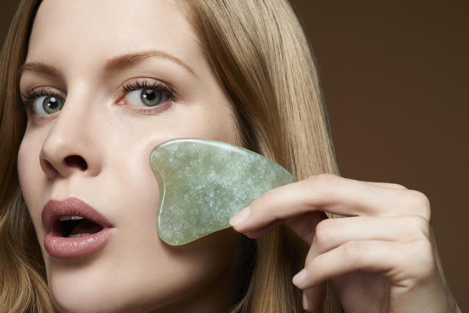 woman massaging her face to avoid wrinkles with a scraping jade Gua Sha Massage tool- asian skin care beauty trend