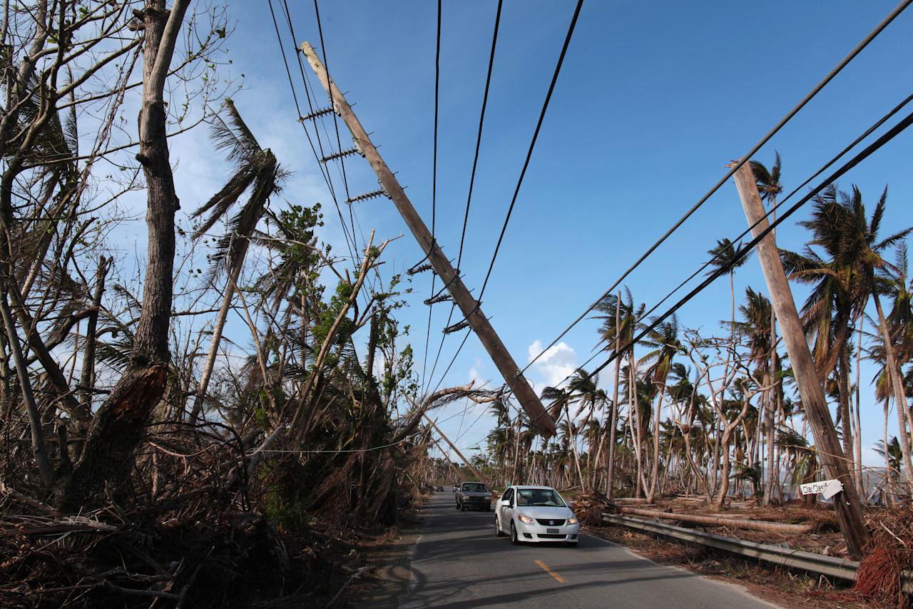 Cars drive under a partially collapsed utility pole, after the island was hit by Hurricane Maria in September, in Naguabo, Puerto Rico October 20, 2017. REUTERS/Alvin Baez     TPX IMAGES OF THE DAY