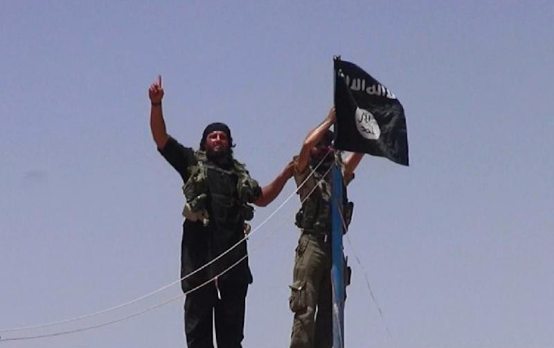 An image made available by the jihadist Twitter account Al-Baraka news on June 11, 2014 allegedly shows militants of the jihadist group Islamic State hanging their flag on a pole at a site on the Syrian-Iraqi border (AFP Photo/-)