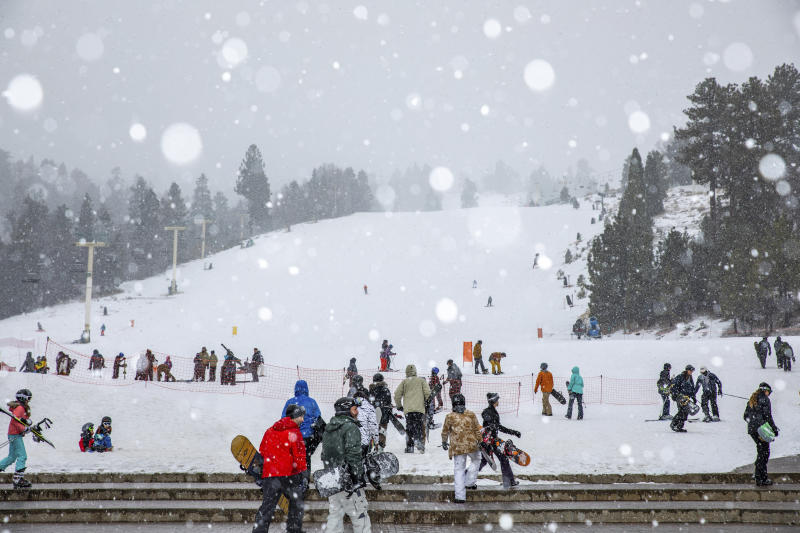In this photo provided by Big Bear Mountain Resort, snowboarders head to the slopes at Big Bear Mountain Resort in Big Bear, Calif., on Monday, Dec. 23, 2019. Winter weather advisories are in effect for the interior mountains of Los Angeles and Ventura counties, where a foot more of snow is expected at elevations above 7,000 feet and lesser amounts down to 5,000 feet. (Jared Meyer/Big Bear Mountain Resort via AP)