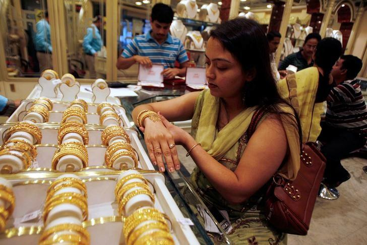 A woman tries on a gold bracelet at a jewellery showroom in the eastern Indian city of Siliguri