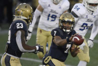 Navy quarterback Xavier Arline (7) pitches the ball toward running back Myles Fells (23) during the first half of an NCAA college football game against Tulsa, Saturday, Dec. 5, 2020, in Annapolis, Md. (AP Photo/Nick Wass)