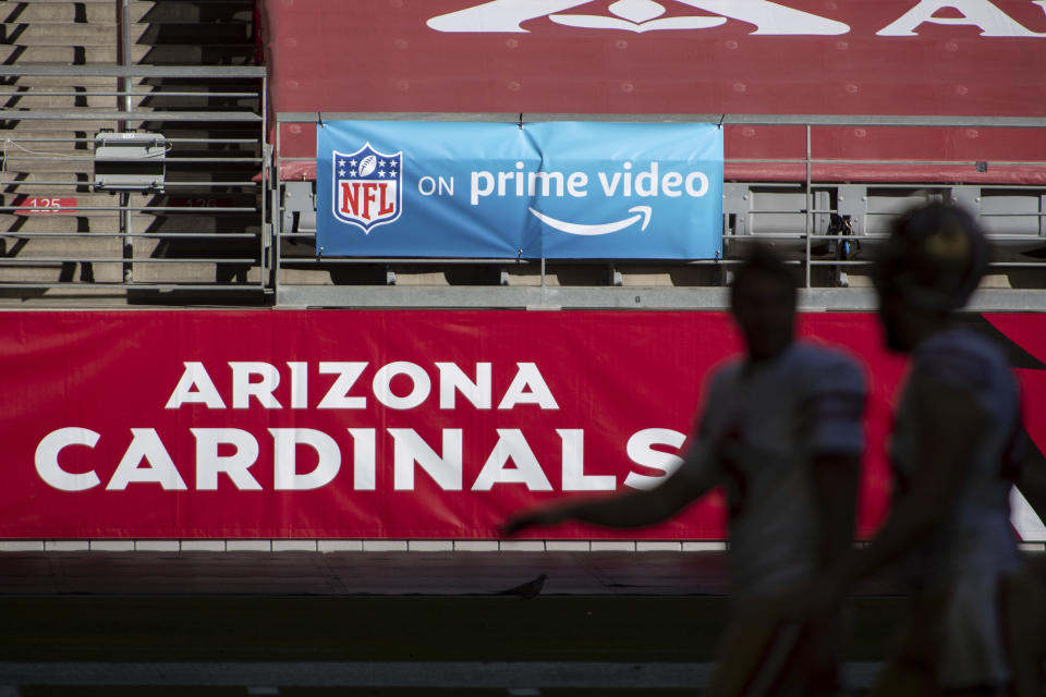 """FILE - In this Saturday, Dec. 26, 2020, file photo, An 'NFL on prime video' banner hangs on the field prior to an NFL football game between the San Francisco 49ers and Arizona Cardinals in Glendale, Ariz. The NFL will nearly double its media revenue to more than $10 billion a season with new rights agreements announced Thursday, March 18, 2021 including a deal with Amazon Prime Video that gives the streaming service exclusive rights to """"Thursday Night Football"""" beginning in 2022.(AP Photo/Jennifer Stewart, File)"""