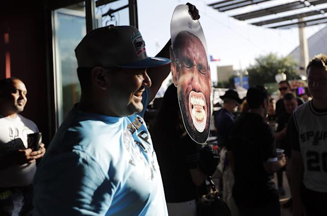 San Antonio Spurs fan holds up a crying Miami Heat forward LeBron James face before Game 1 of the NBA basketball finals on Thursday, June 5, 2014, in San Antonio. (AP Photo/Eric Gay)
