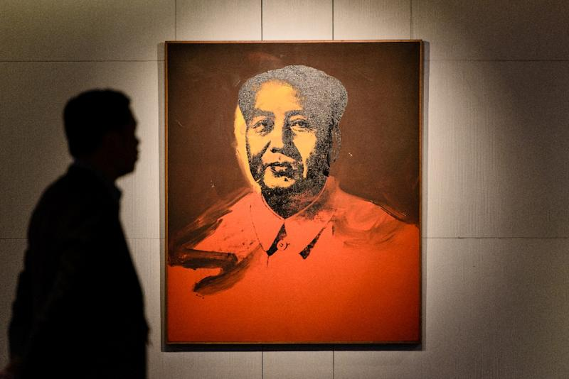 A man walks past 'Mao' a 1973 screen print by US artist Andy Warhol, during a pre-auction preview by Sotheby's in Hong Kong, on March 17, 2017