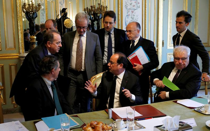 French President Francois Hollande (C) speaks with ministers and officials at the end of a defence council at the Elysee Palace - Credit: REUTERS/Philippe Wojazer