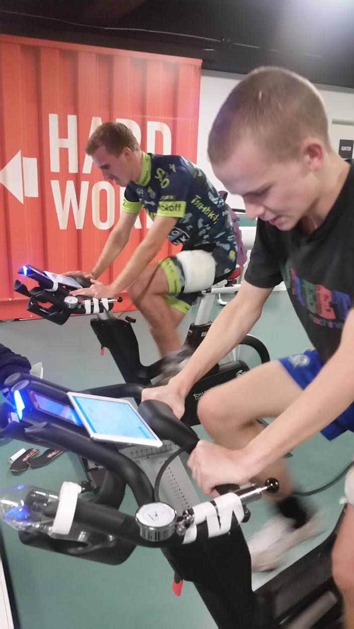 """<span class=""""caption"""">Participants cycling with a nylon cuff around one leg while the other leg serves as the control. Training load was monitored in real time by force sensors in the cycling shoes.</span>"""