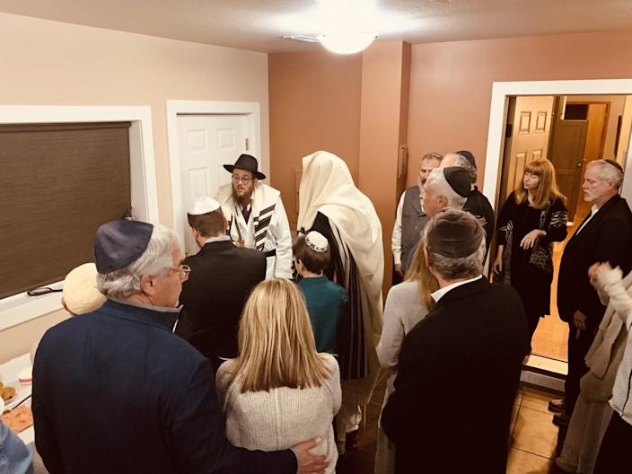 Rabbi Chaim Bruk (back far left in hat) makes the Havdalah service on a glass of wine to celebrate the conclusion of Yom Kippur at his synagogue in Bozeman, Montana.