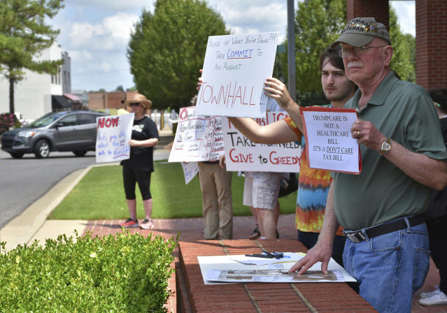 <p>John Hatcher, right, and Ethan Williams, both of Jonesboro, hold up signs for passing motorists while protesting the healthcare bill in front of the Municipal Center Thursday, June 29, 2017, in Jonesboro, Ark. The Senate GOP's stalled health care legislation needs to ease some of its limits on Medicaid spending and give greater control of the program to the states, Arkansas Gov. Asa Hutchinson said Thursday (Photo: Staci Vandagriff/The Jonesboro Sun via AP) </p>