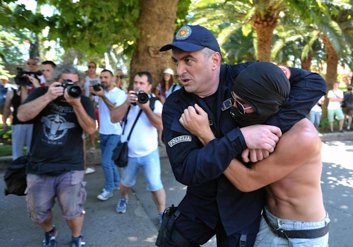 """Montenegro police officers arrests a man during the first ever gay pride event in the Montenegrin seaside resort of Budva, Wednesday, July 24, 2013. Dozens of extremists shouting """"Kill the gays"""" attacked gay activists as they were gathering for the first ever pride event in staunchly conservative Montenegro. The assailants threw rocks, bottles and various other objects at some 20 gay activists and supporters and at special police securing the event in the coastal town of Budva on Wednesday. Police intervened to push the attackers away and the event continued as planned. (AP Photo/Risto Bozovic)"""