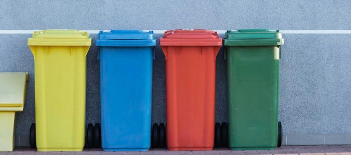 Four colorful garbage bins against a wall.