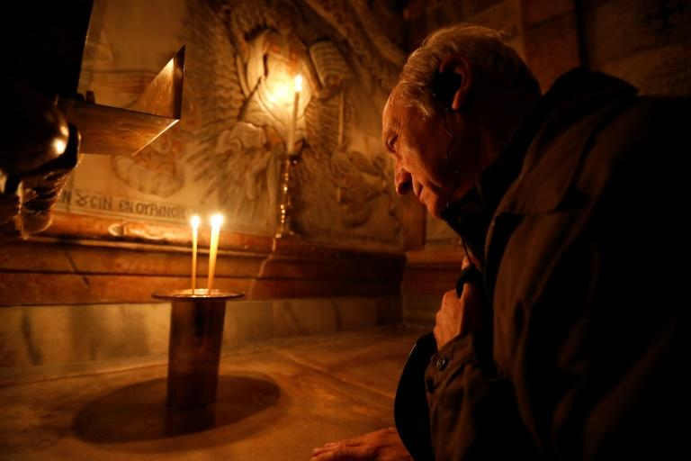 A Christian prays inside the edicule that surrounds the tomb where Jesus is believed to have been buried