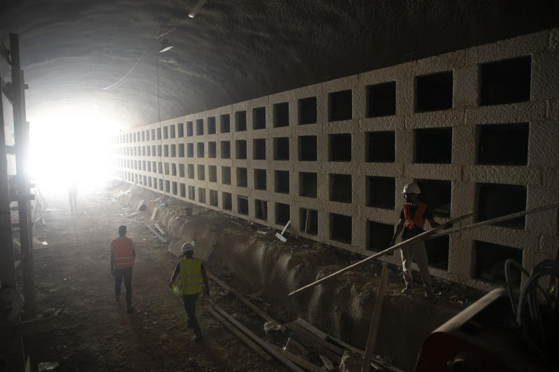 In this Sunday, Aug. 18, 2019 photo, workers walk at the construction site of a massive underground cemetery in Jerusalem. Under a mountain on the outskirts of Jerusalem, workers are completing three years of labor on a massive subterranean necropolis comprised of a mile (1.5 kilometers) of tunnels with sepulchers for interring the dead. (AP Photo/Oded Balilty)
