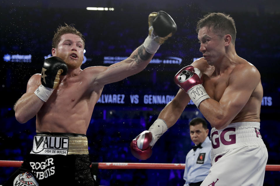 Canelo Alvarez, left, and Gennady Golovkin trade punches in the third round during a middleweight title boxing match, Saturday, Sept. 15, 2018, in Las Vegas. (AP Photo/Isaac Brekken)