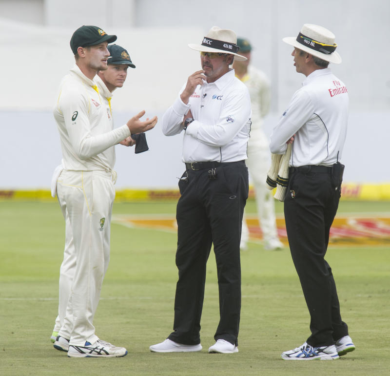 Umpires Nigel Llong and Richard Illingworth confront Cameron Bancroft (pictured left) over a piece of sadpaper.
