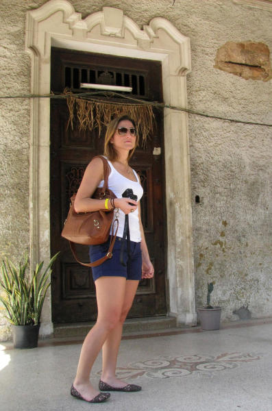 ** CORRECTS SPELLING OF DALMAU **Cecilia Dalmau stands in front of her mother's childhood home in Havana, Cuba, Tuesday March 27, 2012. Dalmau's mother fled Cuba in 1959 as a young girl, days after Fidel Castro and his fellow revolutionaries marched victoriously into Havana. The family never returned. Dalmau is one of more than 300 mostly Cuban-Americans on a pilgrimage to Cuba led by the Roman Catholic archbishop of Miami for Pope Benedict XVI's visit. (AP Photo/Laura Wides-Munoz)