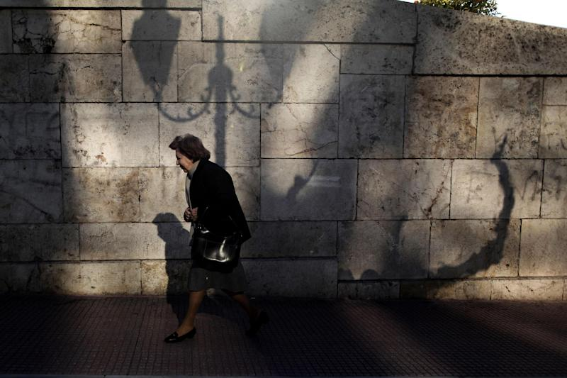 A woman walks outside the Greek parliament  in Athens, Friday, Dec. 14, 2012. Greece has imposed deeply unpopular spending cuts and tax hikes over the past three years, to secure vital international rescue loans.  Greece is in line to get 49.1 billion euro ($64 billion) between now and March, with 34.3 billion euro of that amount due in the coming days.  (AP Photo/Petros Giannakouris)