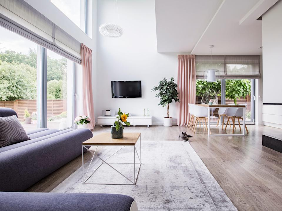 Real photo of a dining area, television and gray couch in open space living room interior