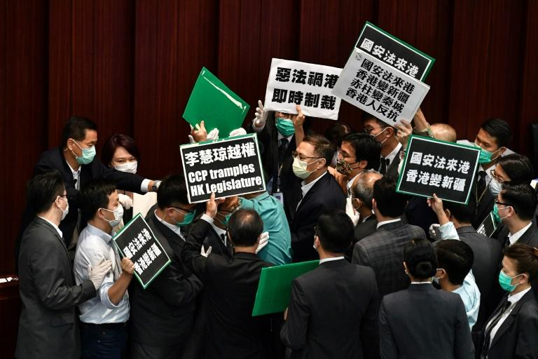 Hong Kong pro-democracy lawmakers holding up placards are blocked by security as they protest China's planned national security legislation during a House Committee meeting (AFP Photo/Anthony WALLACE)