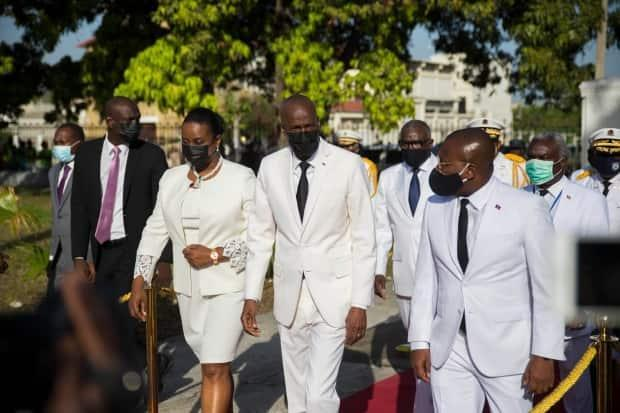 President Jovenel Moise, center, walks with first lady Martine Moise, left, and interim Prime Minister Claude Joseph, right, during a ceremony marking the 218th anniversary of the creation of the Haitian flag, in Port-au-Prince, Haiti, Tuesday, May 18, 2021. (Joseph Odelyn/The Associated Press - image credit)