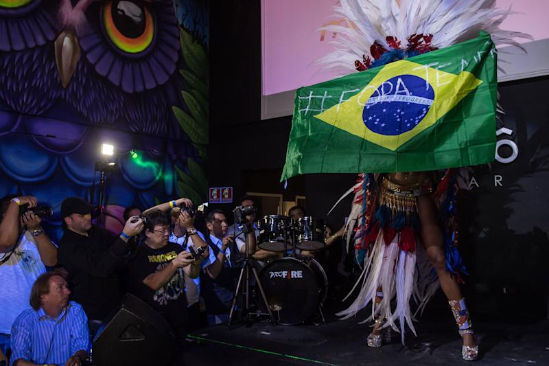Rosie Oliveira from Amazonas holds a Brazilian national flag with an inscription reading 'Temer out' (a reference to Brazilian President Michel Temer) during the Miss Bumbum Brazil 2017 pageant in Sao Paulo.