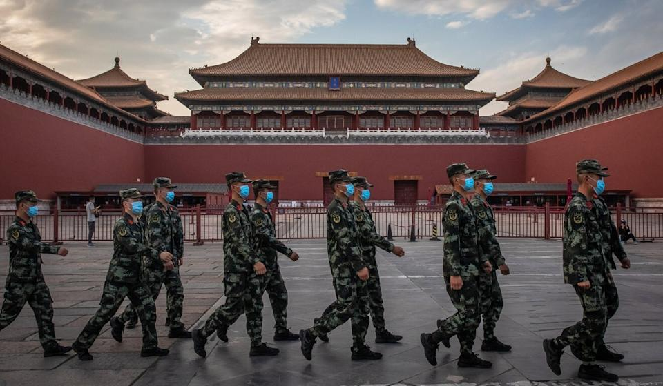 People's Liberation Army (PLA) soldiers wearing protective face masks march past the entrance to the Forbidden City, in Beijing. China will hold the Chinese People's Political Consultative Conference (CPPCC) on Thursday and the National People's Congress (NPC) on Friday. Photo: EPA-EFE