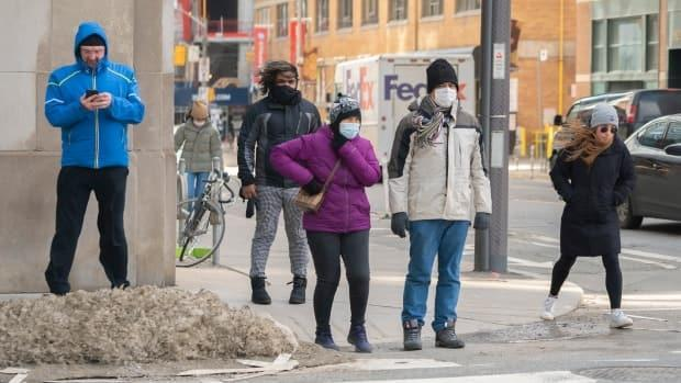 Pedestrians wait to cross an intersection in downtown Toronto on Monday. Environment Canada issued a special weather statement warning of winds gusting up to 80 km/h on Monday afternoon.  (Sam Nar/CBC - image credit)