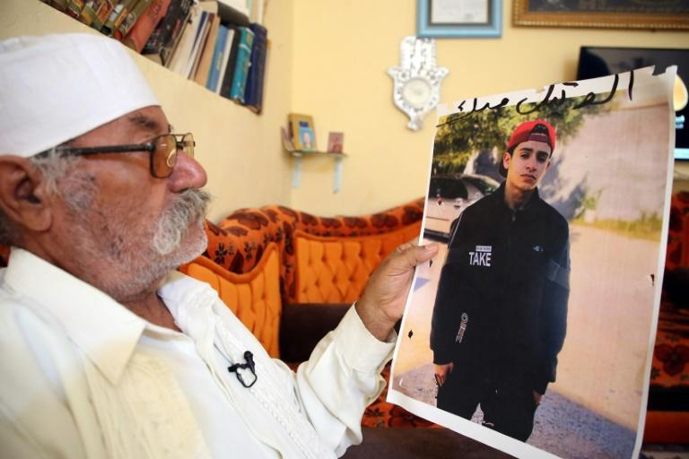 Libyan Mohamed al-Magri holds a picture of his 20-year-old missing son Haitham who he believes was killed and buried in a mass grave in the western city of Tarhuna after armed men took him from his home a year ago