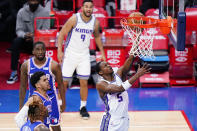 Sacramento Kings' De'Aaron Fox, right, goes up for a shot during the first half of an NBA basketball game against the Philadelphia 76ers, Saturday, March 20, 2021, in Philadelphia. (AP Photo/Matt Slocum)