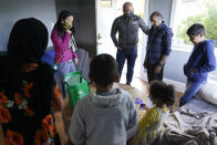 Thuy Do, second from left, and her husband, Jesse Robbins, center, talk with Abdul, second from right, and his family, after they stopped by the vacant rental home they own in Seattle, Monday, Sept. 20, 2021, to drop off produce from their garden and check on the family. Abdul worked as a mechanic before leaving Kabul, Afghanistan about a month ago, and Do and Robbins have provided the house as a place for them live until they can find more permanent housing. Do was nine years old when her family arrived in the United States from Vietnam in the 1980s, and that memory led Do and Robbins to reach out to assist Afghans fleeing their country. (AP Photo/Ted S. Warren)