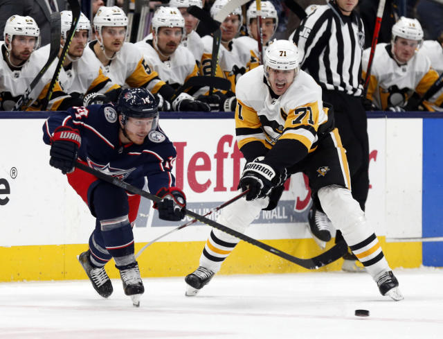 Columbus Blue Jackets forward Gustav Nyquist, left, of Sweden, passes in front Pittsburgh Penguins forward Evgeni Malkin, of Russia, during the second period of an NHL hockey game in Columbus, Ohio, Friday, Nov. 29, 2019. (AP Photo/Paul Vernon)