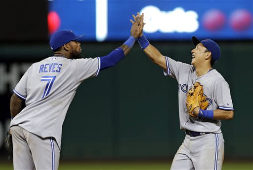 Toronto Blue Jays' Jose Reyes (7) celebrates with Munenori Kawasaki after Toronto's 5-4 win over the Cleveland Indians in a baseball game Wednesday, July 10, 2013, in Cleveland. Kawasaki's single in the ninth drove in two and a third scored on an error by Indians center fielder Michael Bourn. (AP Photo/Mark Duncan)